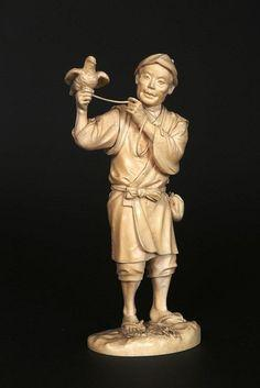 A JAPANESE IVORY OKIMONO Carved as a man holding a bird