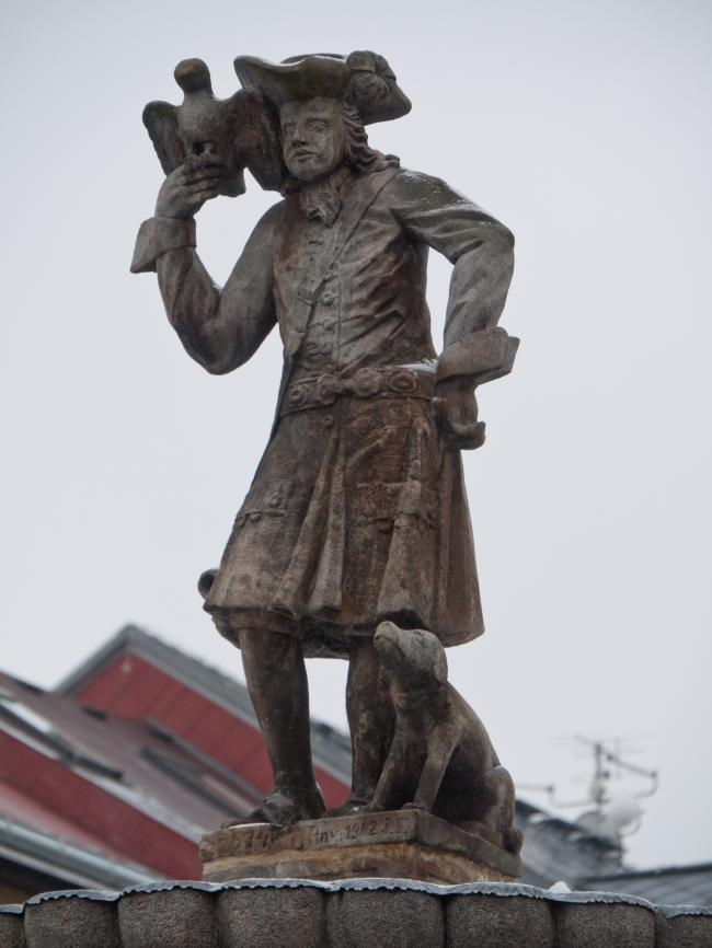 Stone statue of a falconer with his dog and a falcon in Falknov nad Oh?� 3
