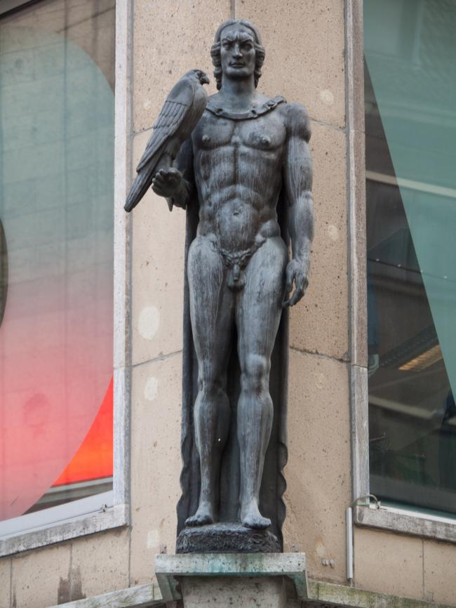 Corner statue of a nude man with a falcon in Dortmund in Germany.